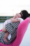 Sira de mãe a guardar seu bebê recém-nascido no vestido 'sexy' quando estava dormindo O bebê está dormindo em seu ombro da mãe no Foto de Stock