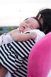 Sira de mãe a guardar seu bebê recém-nascido no vestido 'sexy' quando estava dormindo O bebê está dormindo em seu ombro da mãe no Imagens de Stock Royalty Free