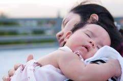 Sira de mãe a guardar seu bebê recém-nascido no vestido 'sexy' quando estava dormindo O bebê está dormindo em seu ombro da mãe no Fotos de Stock
