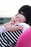 Sira de mãe a guardar seu bebê recém-nascido no vestido 'sexy' quando estava dormindo O bebê está dormindo em seu ombro da mãe no Imagens de Stock