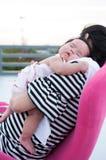 Sira de mãe a guardar seu bebê recém-nascido no vestido 'sexy' quando estava dormindo O bebê está dormindo em seu ombro da mãe no Foto de Stock Royalty Free