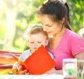 Sira de mãe a ler um livro a seu bebê pequeno no parque ensolarado fotografia de stock