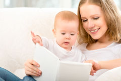 Sira de mãe a ler um livro um bebê pequeno no sofá Fotografia de Stock Royalty Free