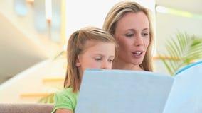 Sira de mãe a ler uma história a sua filha loura video estoque