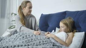 Sira de mãe a nutrir sua filha doente na cama em casa filme
