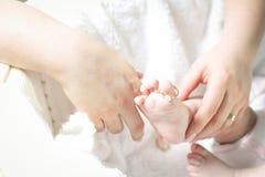 Sira de mãe a pôr um anel sobre o dedo do pé da sua criança Foto de Stock Royalty Free