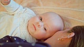 Sira de mãe a Playning com seu bebê que encontra-se na cama imagens de stock