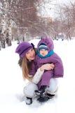 Sira de mãe a prender um bebê, neve, parque do inverno, caminhada Imagens de Stock