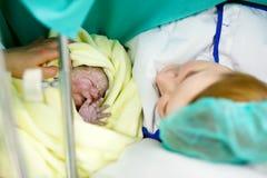 Sira de mãe a procurar o primeiro ime seu bebê que está sendo carregado através da cesariana foto de stock