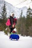 Sira de mãe a puxar uma criança através da neve em um toboggan Fotografia de Stock