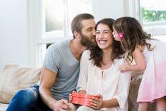 Sira de mãe a receber um presente de seus marido e filha fotos de stock royalty free