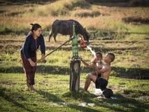 Sira de mãe a seu chuveiro dos filhos exterior da bomba da água subterrânea Fotografia de Stock Royalty Free