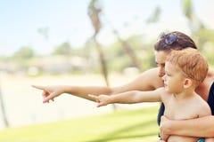 Sira de mãe a ter o divertimento na praia com seu filho pequeno Imagem de Stock