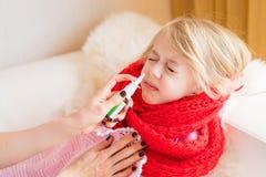 Sira de mãe a tratar seu nariz ralo do ` s da criança com o pulverizador nasal imagens de stock royalty free