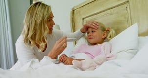 Sira de mãe a verificar a temperatura doente da filha com o termômetro digital no quarto 4k filme