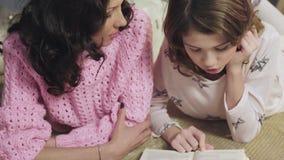 Sira de mãe a verificar trabalhos de casa das filhas na literatura, escutando sua leitura vídeos de arquivo
