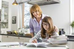 Sira de mãe a ajudar a filha em fazer trabalhos de casa na cozinha Foto de Stock