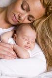 Sira de mãe ao bebé da terra arrendada em seus braços Imagem de Stock