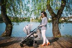 Sira de mãe ao passeio sua criança perto do lago no parque da cidade com um pram bonito Imagens de Stock