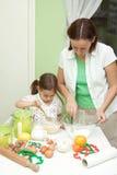 Sira de mãe e sua filha, bakeing na cozinha Imagens de Stock
