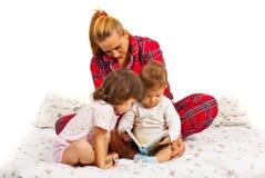 Sira de mãe a ler uma história de horas de dormir a suas crianças Fotografia de Stock
