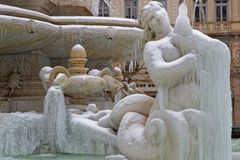 The siren of the fountain is very cold. LYON, FRANCE, March 1, 2018 : Fountain of Place des Jacobins, as a cold spell rages in all Europe and the Capital of Royalty Free Stock Photography