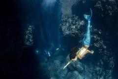 Sirena che nuota underwater nel mare blu profondo immagine stock