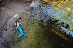 Sirena en el agua en la orilla Foto de archivo