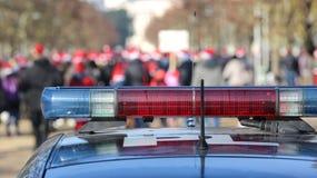 sirenas en el coche policía en el parque urbano público con muchos peo Foto de archivo