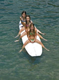 Sirens - surfing children. Sea sirens, sisters (best friends) spending summer holidays sitting on surf desk on Adriatic sea (Croatia-Dalmatia Royalty Free Stock Photos