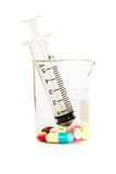 Siringa in becher e nel gruppo di droghe Immagine Stock