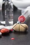 Siringa con il farmaco, le capsule e le compresse su un fondo nero Immagini Stock Libere da Diritti