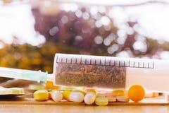 Siringa con le erbe e le compresse medicinali sulla tavola fotografia stock libera da diritti