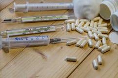 Siringa, termometri, pillole su un fondo di legno immagini stock