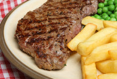 Sirloin Beef Steak & Chips Meal. Chargrilled sirloin steak with chips and peas. With visible seasoning Stock Photography