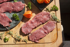 Sirloin on a cutting board, and a stoneplate. Sirloin, herbs and physalis on a cutting board, and a stoneplate Royalty Free Stock Image