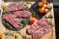 Sirloin and herbs on a cutting board. Sirloin, physalis and herbs on a cutting board Stock Photo