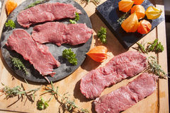 Sirloin, herbs and physalis. On a cutting board, and a stoneplate Stock Photography