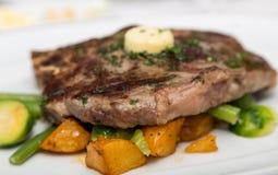 Sirloin Steak with Butter on Vegetable Garnish Stock Image