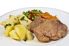Sirloin steak dinner. Sirloin steak with boiled potatoes, peas and carrots, on white plate Stock Image