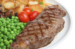 Sirloin Steak Dinner. Sirloin steak with sauteed potatoes, mushrooms and peas Royalty Free Stock Photos