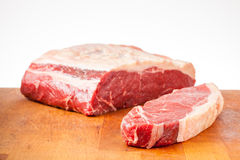 Sirloin Steak and Joint. Large sirloin joint ready to be cut into steaks on a butchers block with one steak cut off Royalty Free Stock Photography