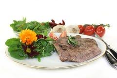Sirloin steak. A roasted ribeye steak with wild herb salad royalty free stock photos