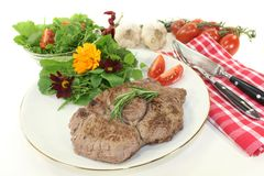 Sirloin steak. A roasted ribeye steak with wild herb salad royalty free stock photography