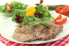 Sirloin steak. A roasted ribeye steak with wild herb salad royalty free stock photo