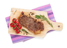 Sirloin steak with rosemary and cherry tomatoes on a cutting boa Royalty Free Stock Image