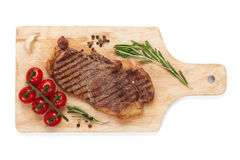 Sirloin steak with rosemary and cherry tomatoes on a cutting boa. Rd. Isolated on white background. View from above Stock Photos