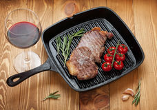 Sirloin steak with rosemary and cherry tomatoes on a frying pan Stock Photos