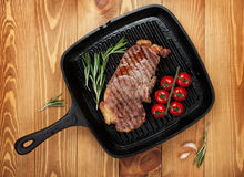 Sirloin steak with rosemary and cherry tomatoes on frying pan. Over wooden table Royalty Free Stock Images