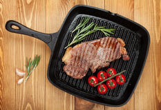 Sirloin steak with rosemary and cherry tomatoes on frying pan. Over wooden table Stock Photos